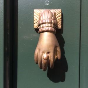 Batedor em forma de mão numa porta algures no Porto